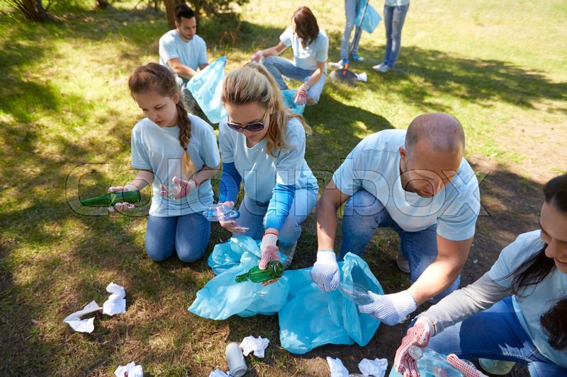 Stock image of 'volunteering, charity, people and ecology concept - group of happy volunteers with garbage bags cleaning area in park'