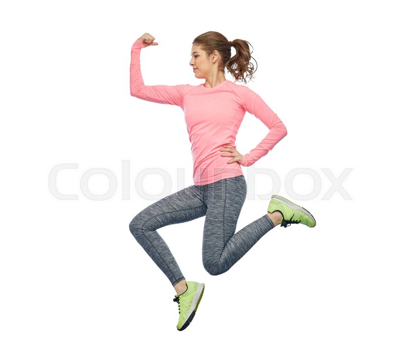 Stock image of 'sport, fitness, motion and people concept - happy smiling young woman jumping in air and showing power gesture over white background'
