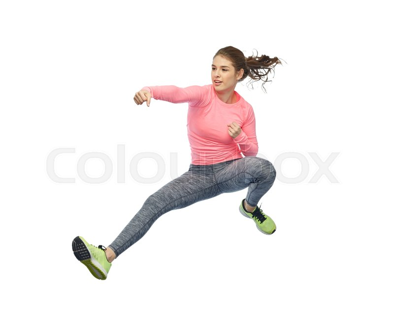 Stock image of 'sport, fitness, motion and people concept - happy young woman jumping in air in fighting pose over white background'