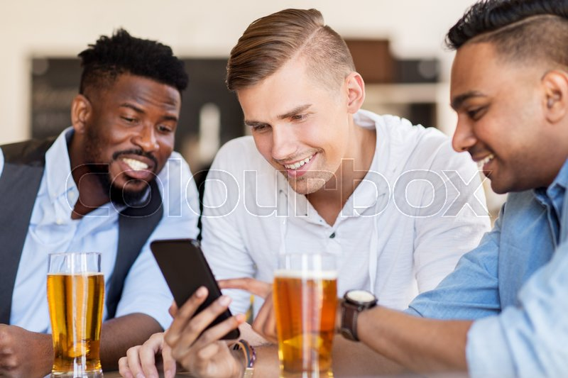 Stock image of 'people, male friendship and technology concept - happy friends with smartphone drinking beer at bar or pub'