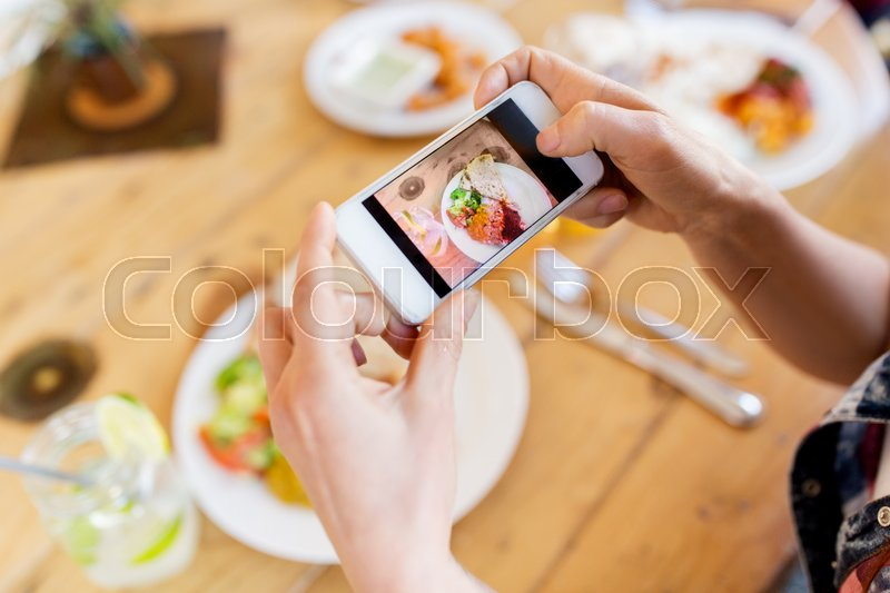 Stock image of 'technology, eating and people concept - hands with smartphone photographing food at restaurant'