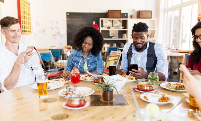 Stock image of 'leisure, technology and people concept - group of happy international friends with smartphones at restaurant table'