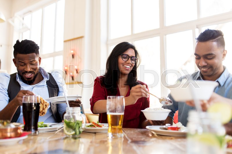 Stock image of 'leisure, food and people concept - group of happy international friends eating at restaurant table'