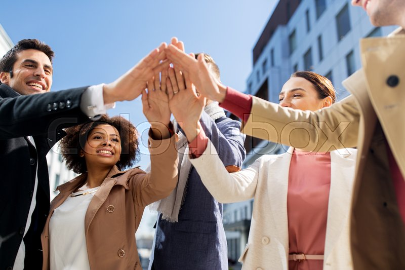 Stock image of 'business, education and corporate concept - international group of people or students making high five on city street'