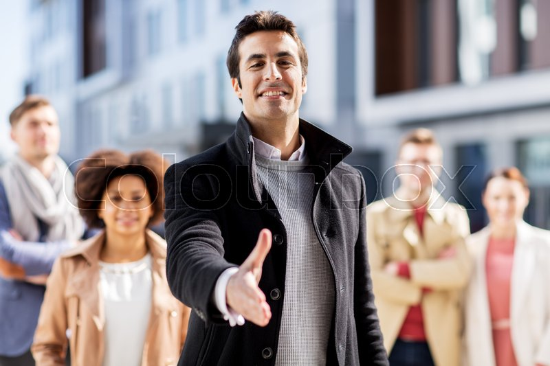 Stock image of 'business, education, gesture and corporate concept - group of happy people and man giving hand for handshake on city street'
