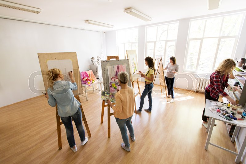 Stock image of 'creativity, education and people concept - group of woman artists or students with brushes and palettes painting and drawing still life picture on easels at art school studio'