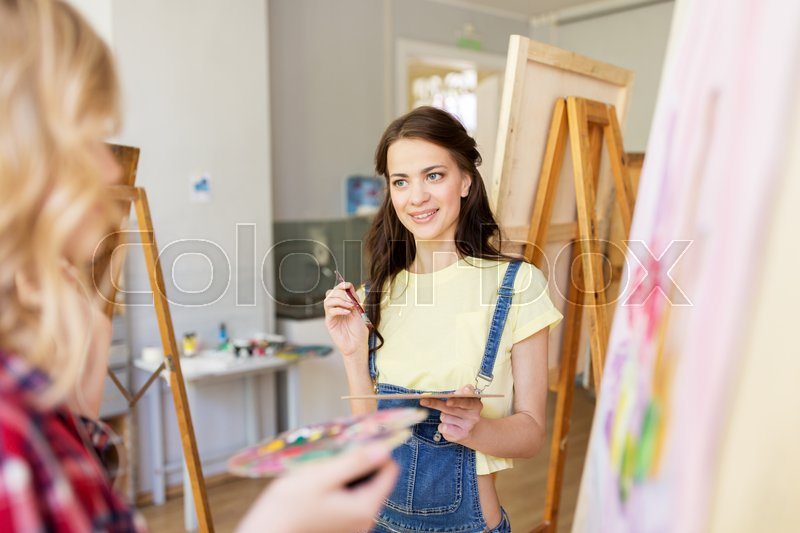 Stock image of 'art school, creativity and people concept - women artists or student girls with easel, palettes and paint brush painting at studio'