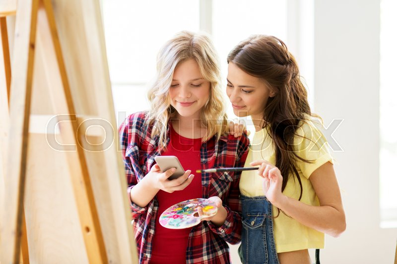 Stock image of 'art school, technology and people concept - happy student girls or artists with smartphone, easel, palette and paint brush painting at studio'
