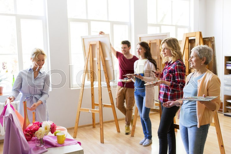 Stock image of 'painting, education and people concept - group of artists or students and teacher with still life and easels at art school studio'