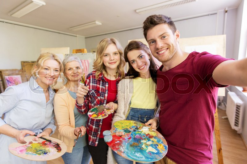 Stock image of 'creativity, education, technology and people concept - group of artists or students with brushes and palettes taking selfie at art school studio'