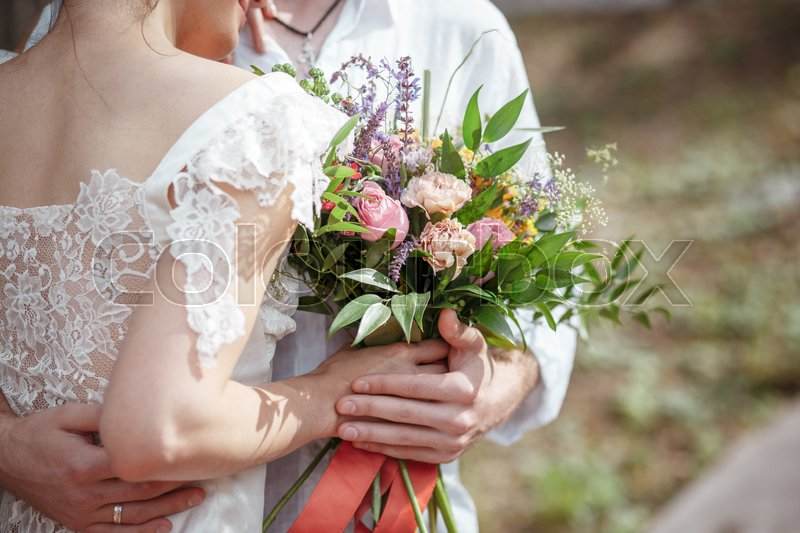 Stock image of 'Wedding decoration in the style of boho, floral arrangement, decorated table in the garden. Against the background of the bride and groom embracing.'