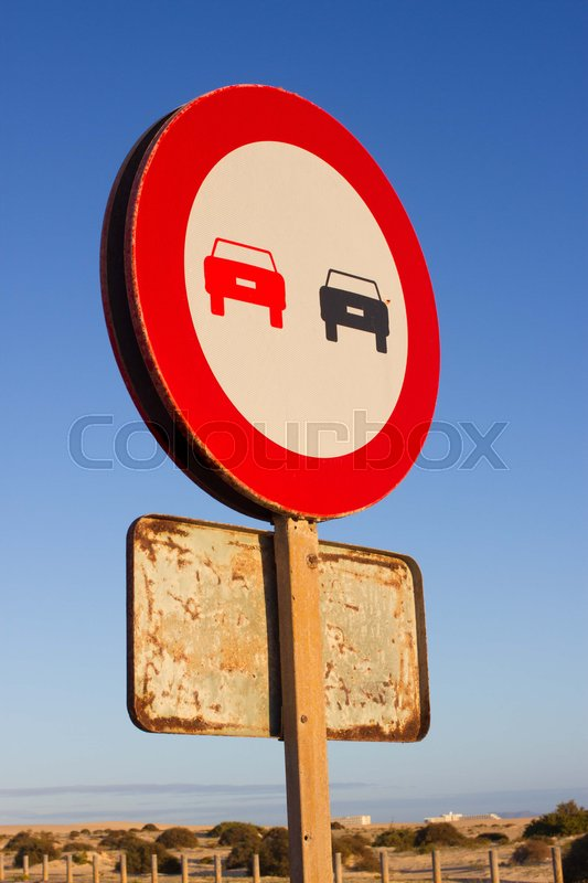 Stock image of 'No overtaking. Prohibited to advance indicating. Round red traffic sign. Ocean road. Asphalt.'