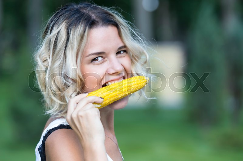 Stock image of 'The girl is eating boiled sweet corn in the park'