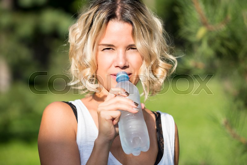 Stock image of 'Girl drinks water in a summer park in nature'