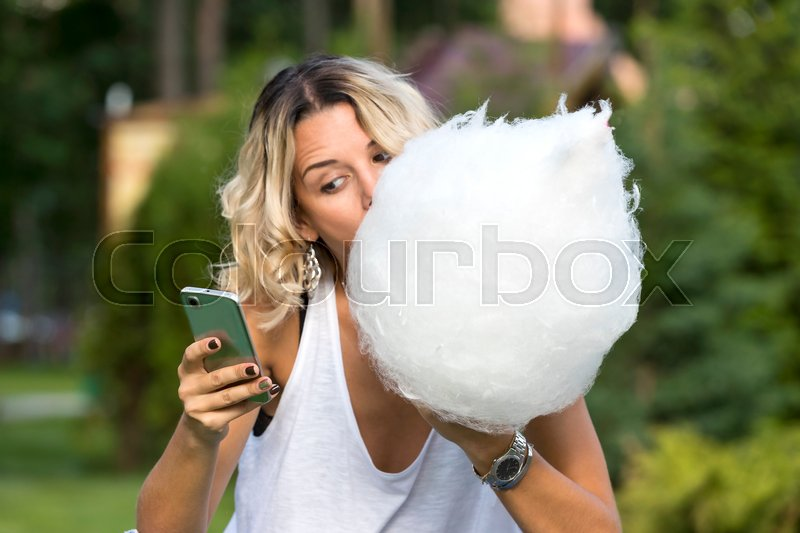 Stock image of 'Girl eating sweet cotton candy in a summer park'