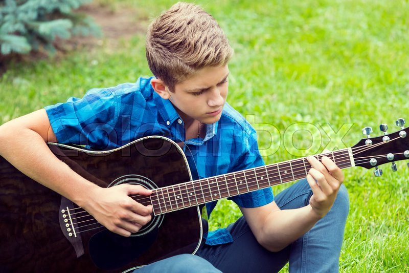 Stock image of 'Young sad guy with an acoustic guitar'