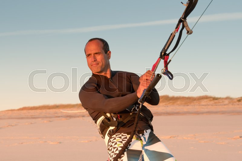 Stock image of 'Kite surfer watching the waves at sunset in Portugal.'