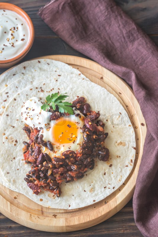 Stock image of 'Tortilla with chipotle bean chili and baked egg'