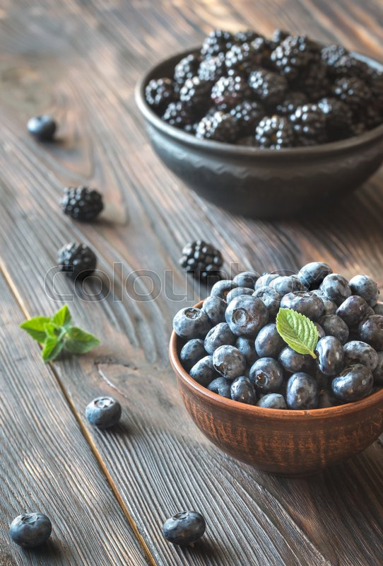 Stock image of 'Bowls of blackberries and blueberries on the wooden table'