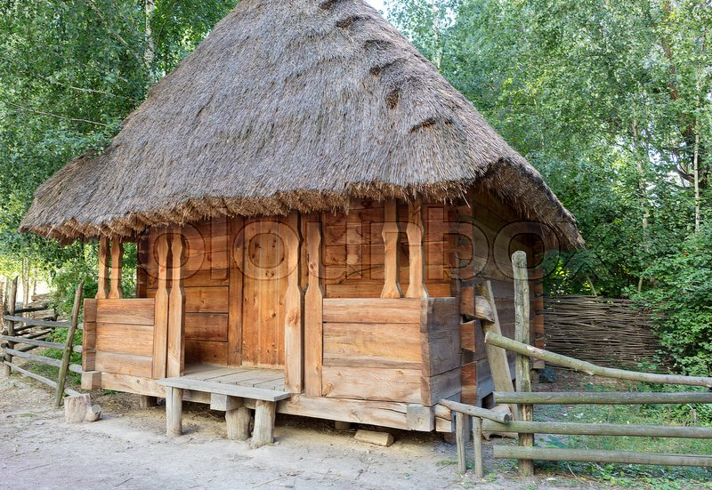 Stock image of 'Old traditional Ukrainian rural barn with a thatched roof and a wooden, wicker fence around it in a green garden'