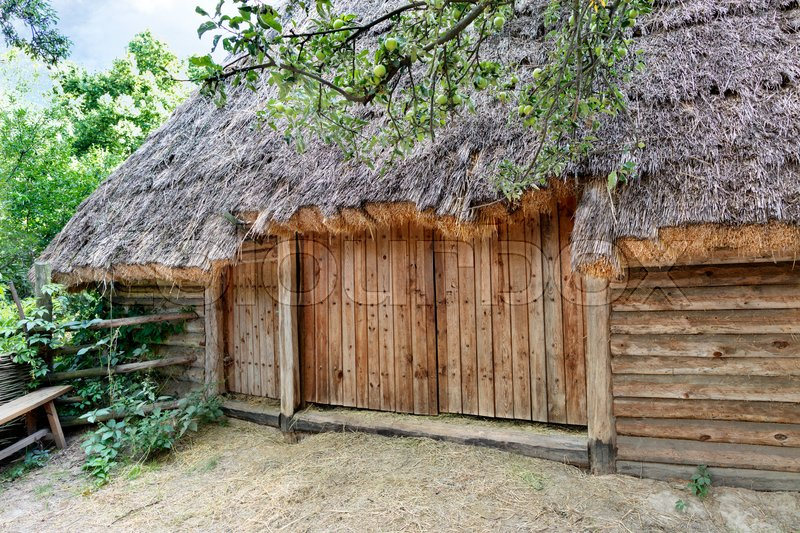 Stock image of 'Old traditional Ukrainian rural barn with a thatched roof for dry grass and a wooden, wicker fence around it in a green garden'