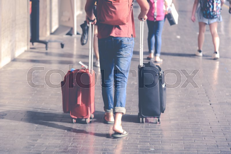 Stock image of 'A girl walks with two suitcases along the platform of a station'