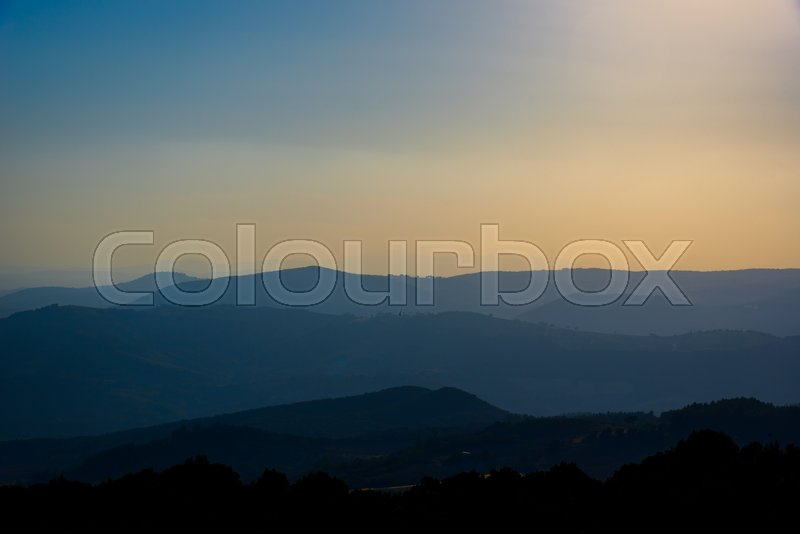 Stock image of 'Silhouette layers of hills at sunset with fog and orange sky'