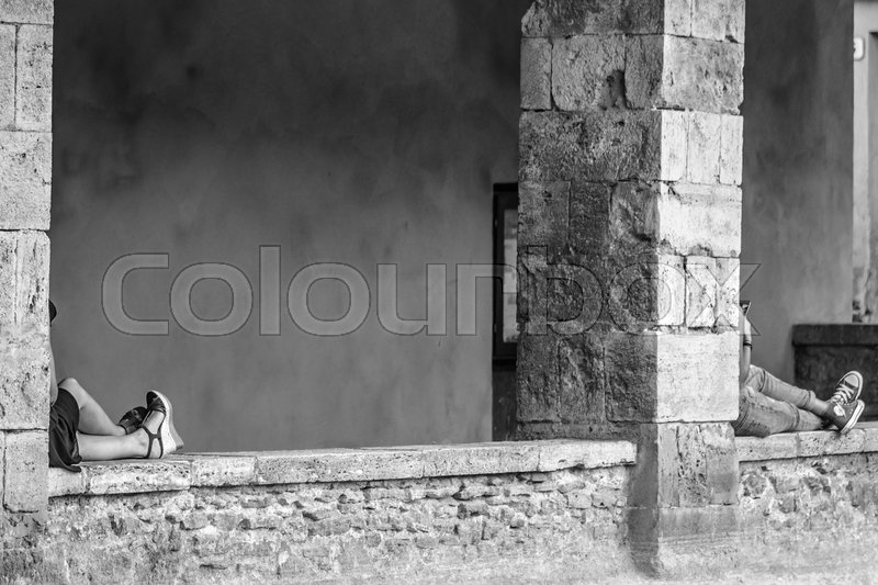 Stock image of 'Two guys relax lying on a wall in the historic center of the beautiful village of Bagno Vignoni in Tuscany'