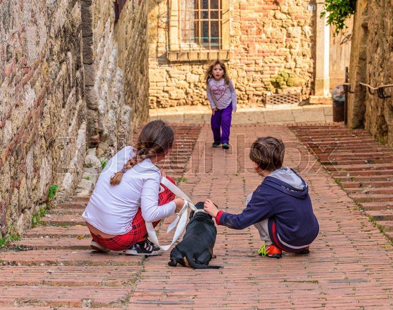 Stock image of 'COLLE VAL D'ELSA, ITALY - APRIL 25, 2017 - Two kids play with a puppy dog in an alley of Colle Val d'Elsa.'