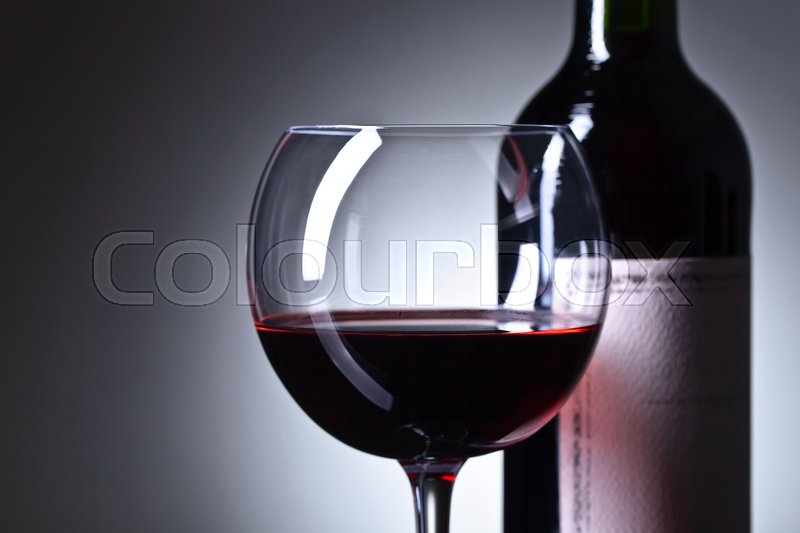 Stock image of 'Bottle and glass of red wine . Old paper label . Copy space .'