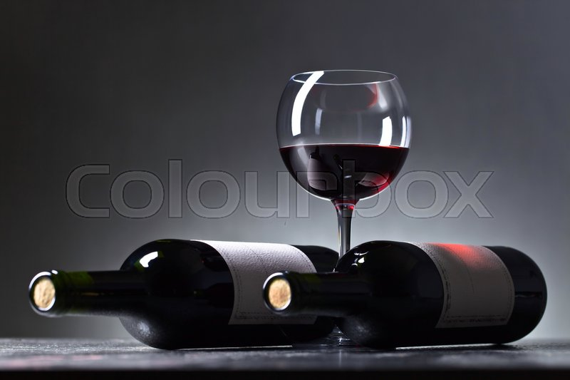 Stock image of 'Bottles and glass of red wine . Old paper label . Copy space .'