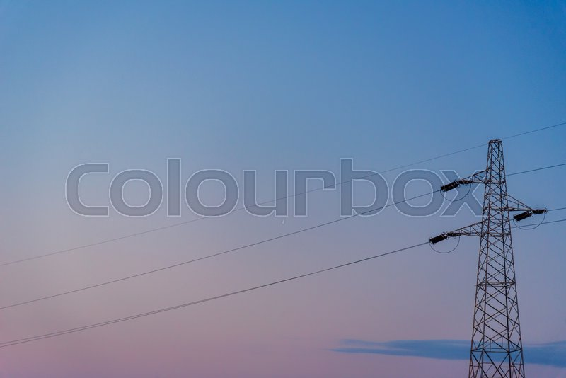 Stock image of 'Silhouette of a powerline at sunset.'