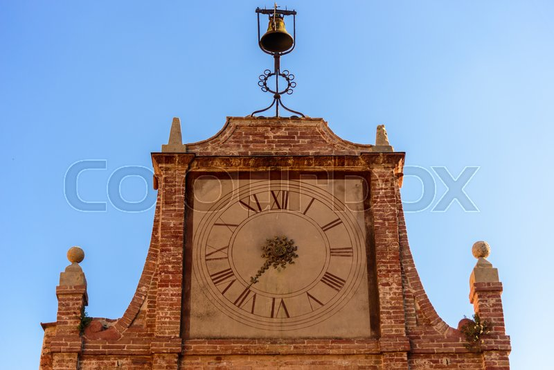 Stock image of 'Tuscan small tower clock with a bell against blue sky'