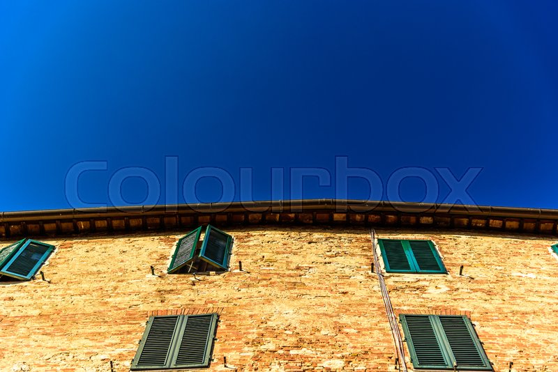 Stock image of 'Tuscan building corner against blue sky'