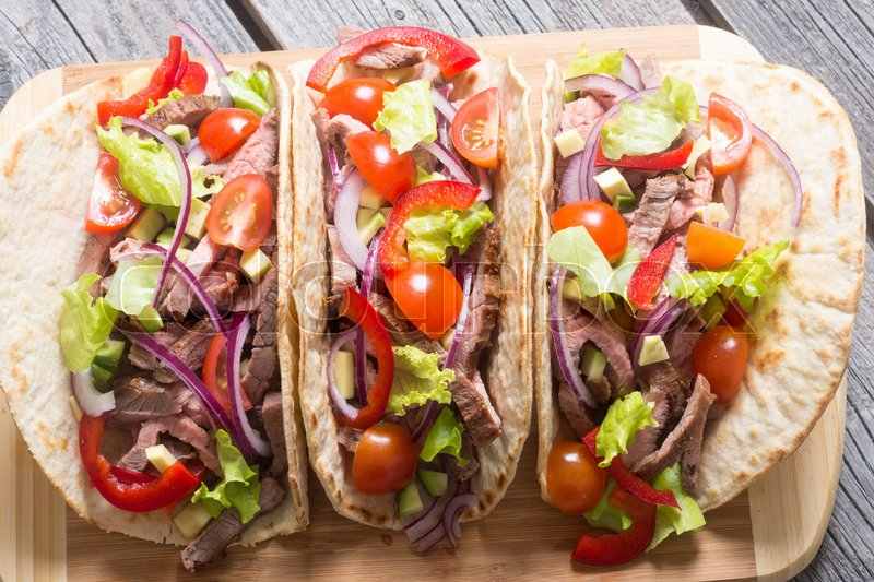 Stock image of 'Mexican pork tacos with vegetables on wooden rustic background . Top view'