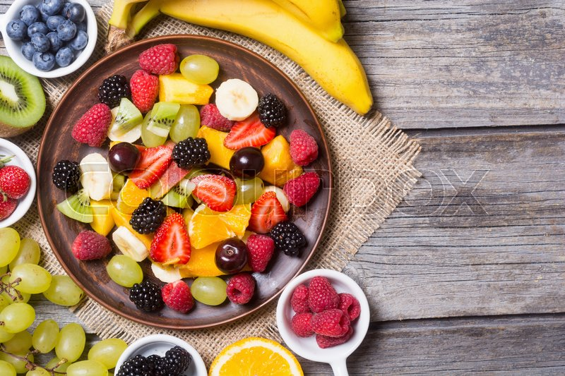 Stock image of 'Fruit and berries salad in ceramic plate on wooden background . Top view with space for text'