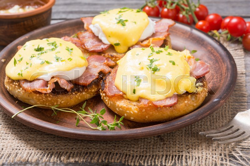 Stock image of 'Eggs benedict with bacon on wooden background . '
