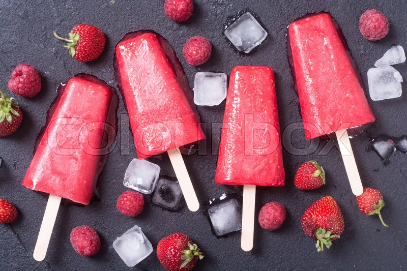 Stock image of 'Colorful homemade popsicle with raspberry and strawberry . Top view'