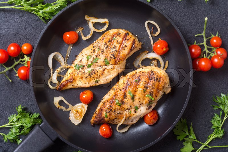 Stock image of 'Grilled chicken breast with tomato , parsley and onion'