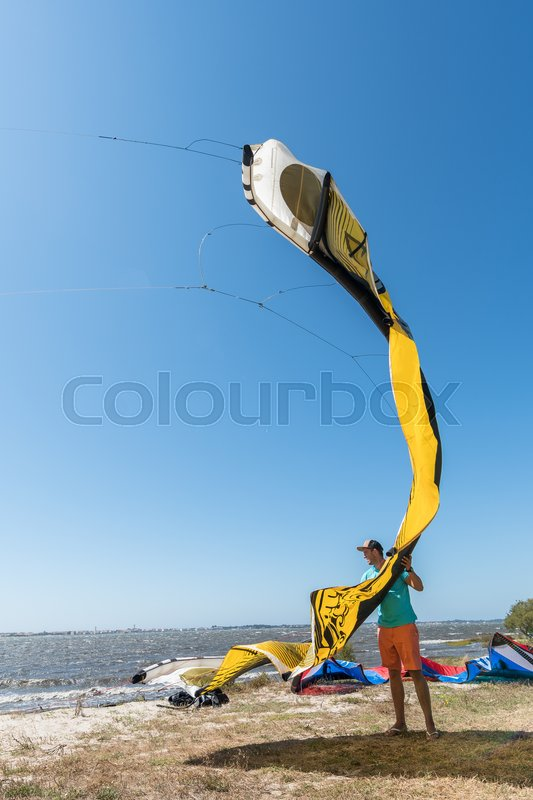 Stock image of 'Kiteboarder preparations for surfing on a sunny day.'