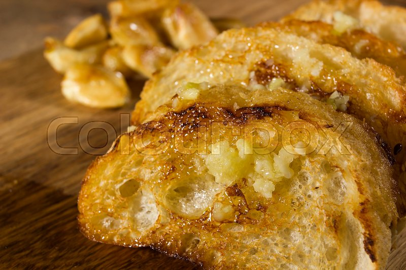 Stock image of 'Fried garlic bread and garlic closeup on a wooden board'