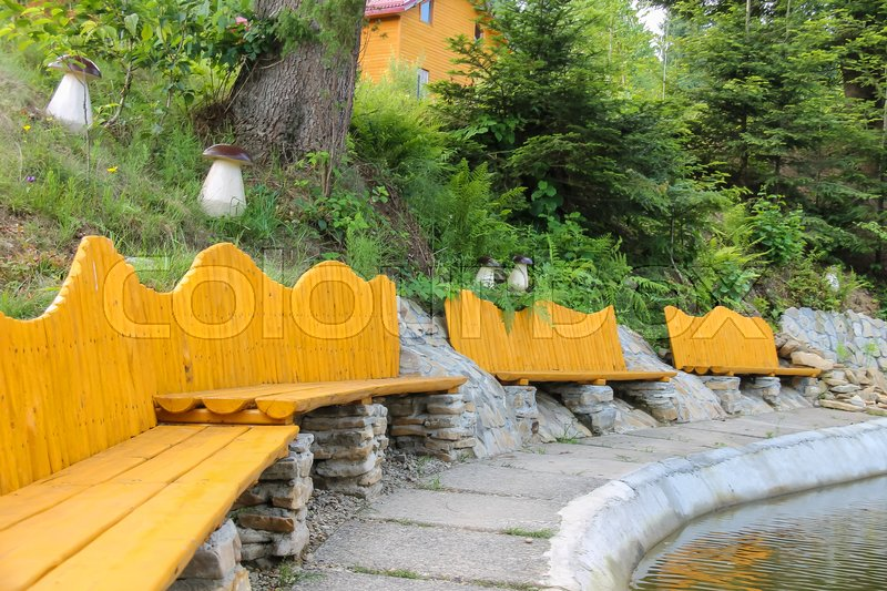 Stock image of 'Original wooden benches on shore of lake in Ukrainian Carpathians'