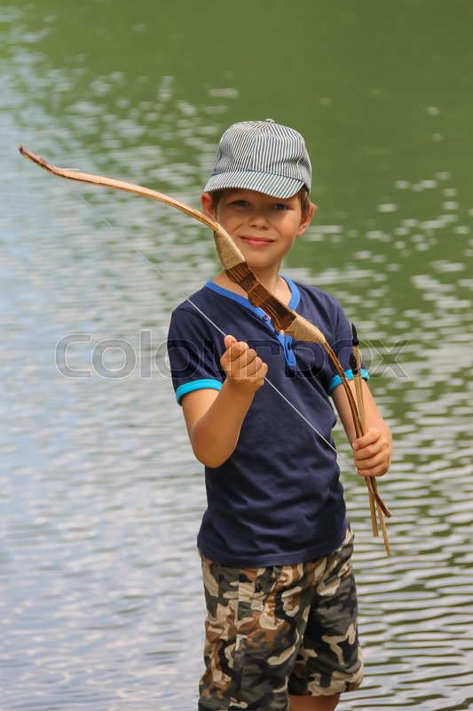 Stock image of 'Smiling boy with arrows and bow near water of lake'