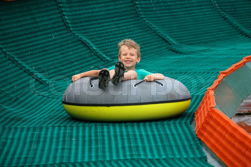Stock image of 'Smiling boy slides down in inflatable ring'