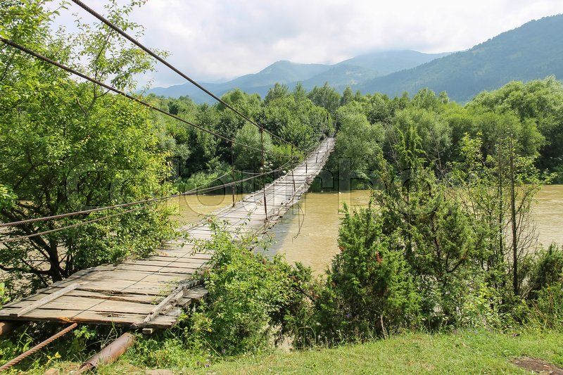 Stock image of 'Suspended wooden bridge across Schodnica river in Carpathians, Ukraine'