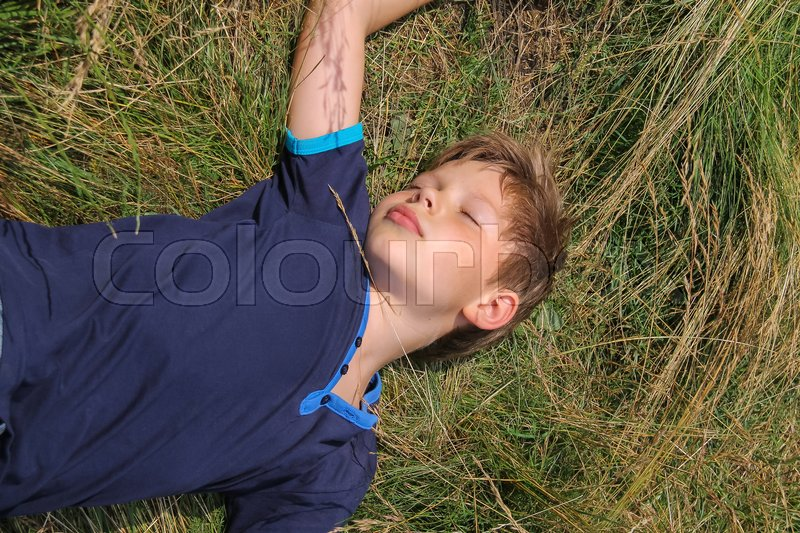 Stock image of 'Handsome boy sleeping on meadow grass'