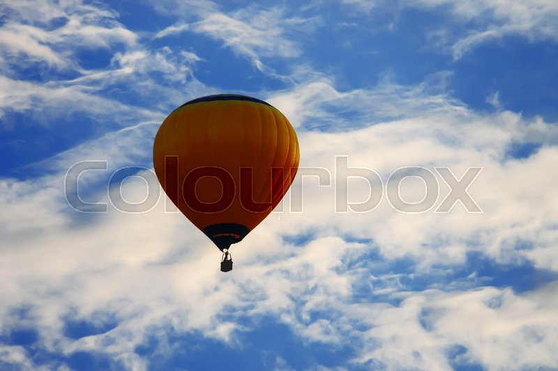 Stock image of 'Bright balloon in blue sky with white clouds'