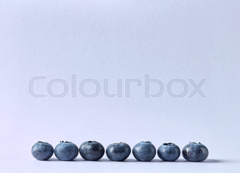 Stock image of 'Seven fresh blueberries on color paper background'