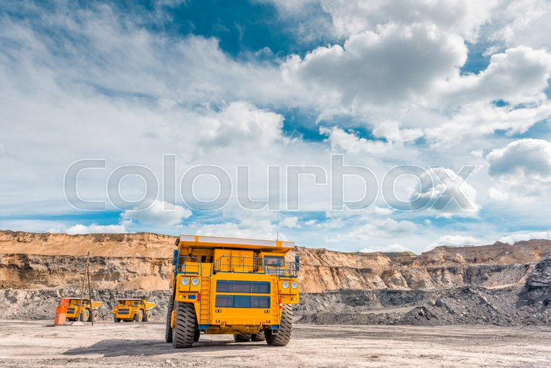 Stock image of 'Big trucks working in an open pit. Coal mine.'