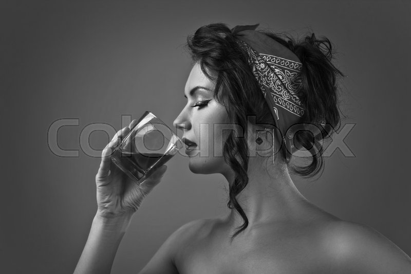 Stock image of 'Black and white portrait of a young beautiful woman with glass of whiskey'